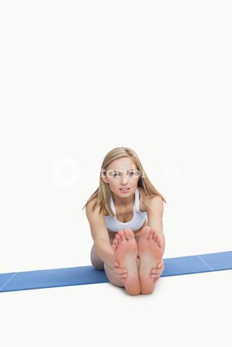 Portrait of young woman performing stretching exercise on yoga mat