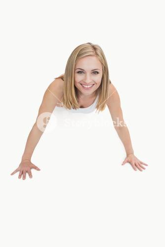 Portrait of happy young woman doing pushups