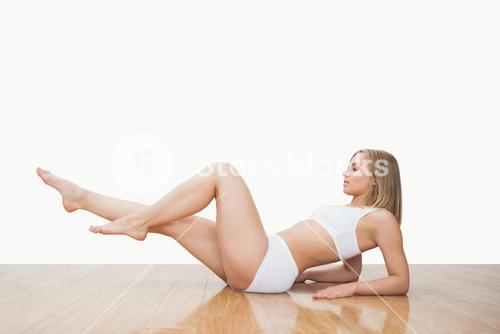 Side view of young woman in yoga pose on hardwood floor