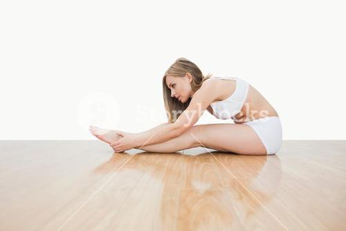 Side view of young woman stretching on hardwood floor