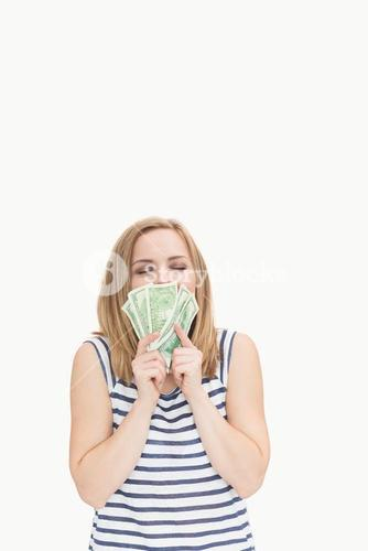 Happy young woman kissing fanned dollars