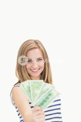 Portrait of happy young woman holding out fanned dollar banknotes