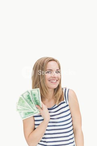 Portrait of happy young woman with fanned dollars