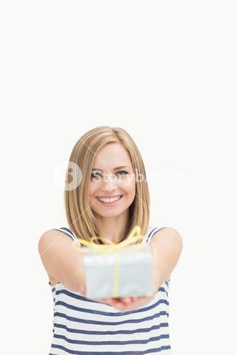 Portrait of cute young woman holding out gift box