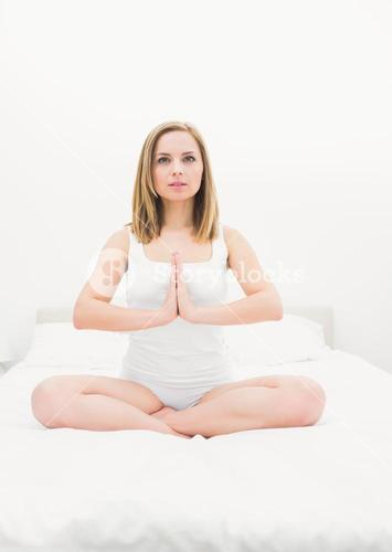 Woman in praying position on bed