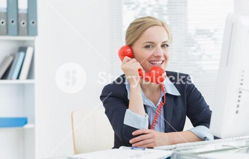 Smiling female executive using red land line phone at desk