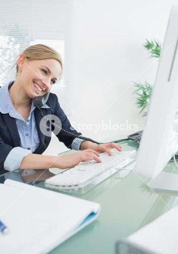 Female executive using landline phone and computer at desk