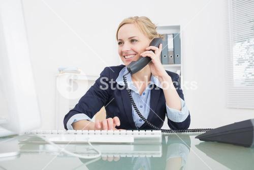 Young female executive using phone at office