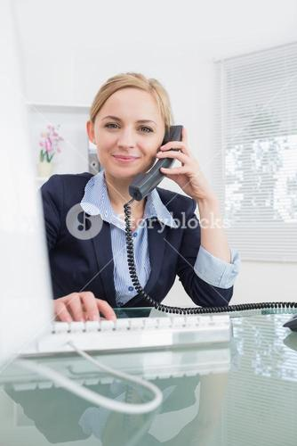 Portrait of female executive using phone and computer at office