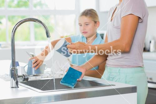 Daughter helping mother do the washing up