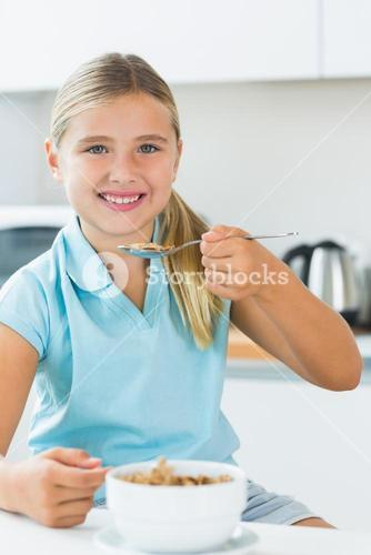 Happy girl eating cereal