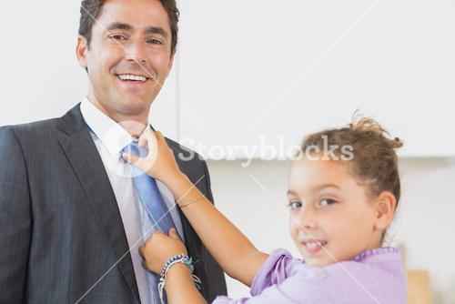 Smiling daughter fixing fathers tie