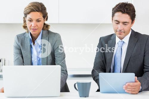 Couple using media devices in kitchen