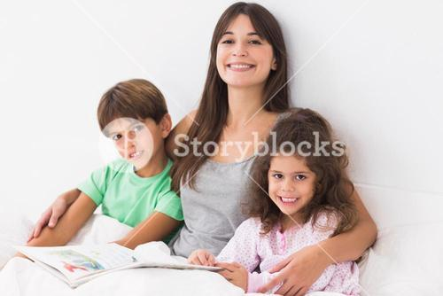 Mother with son and daughter reading book