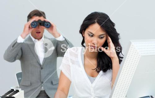 Young businesswoman getting bored and her manager looking through binoculars