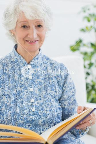 Elderly smiling woman with photo album