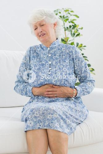 Elderly woman suffering with a belly pain