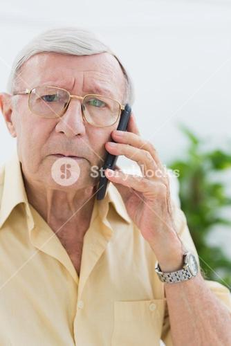 Unhappy elderly man on the mobile phone