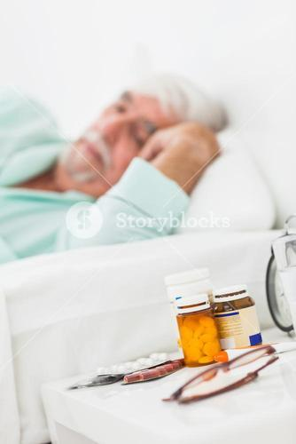 Bedside table with pills and glasses