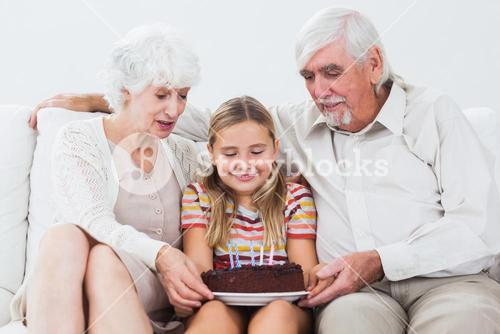 Little girl with grandparents celebrating birthday