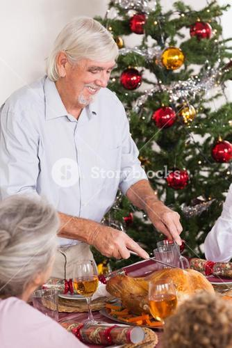 Grandfather carving turkey at christmas