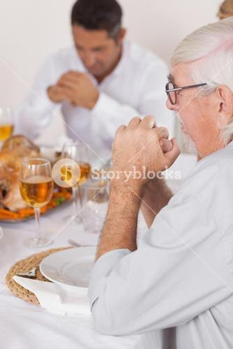 Family saying grace before eating