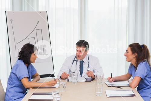 Doctor having meeting with two nurses