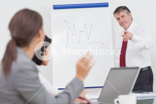Businesswoman using a laptop during a conference and asking a question