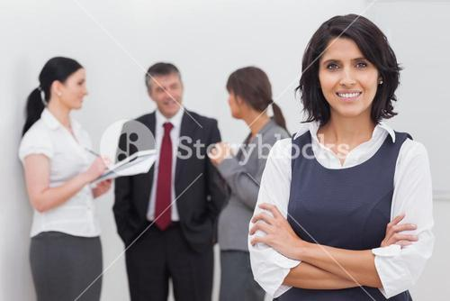 Businesswoman smiling and three business people speaking