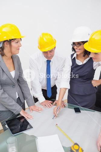 Team looking at a construction plan and laughing
