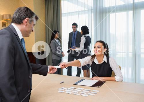 Woman handing name tag to businessman