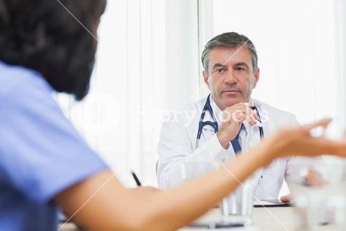 Doctor listening to nurse