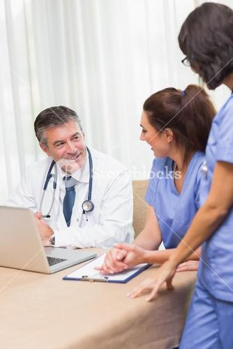 Happy nurses chatting with doctor