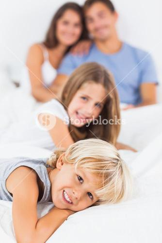 Smiling children lying on the bed