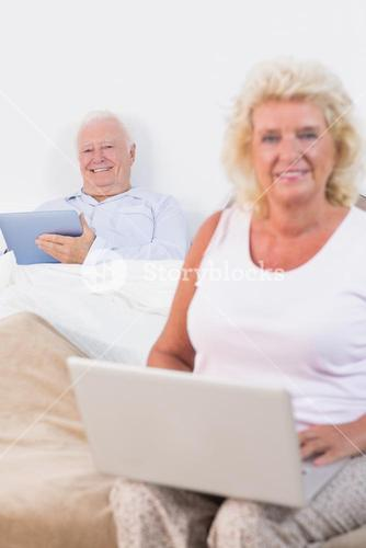 Happy old couple using a tablet and the laptop