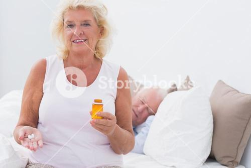 Old woman with the opened pill bottle
