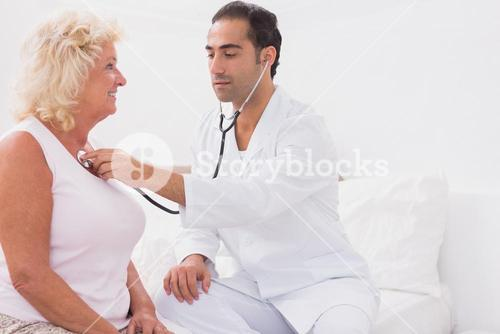 Doctor examining an old woman