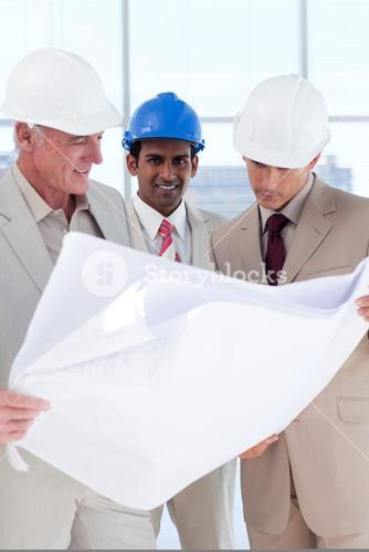 Three engineer coworkers studying plans