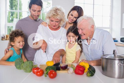 Happy family cutting vegetables together