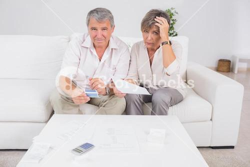 Old stressed couple calculating bills