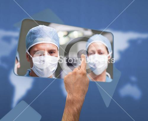 Hand selecting image of surgeons on touchscreen