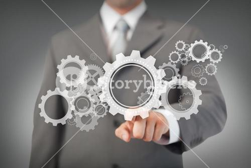 Businessman touching cogs and wheels graphic