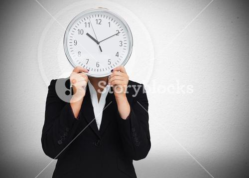 Businesswoman hiding face with clock