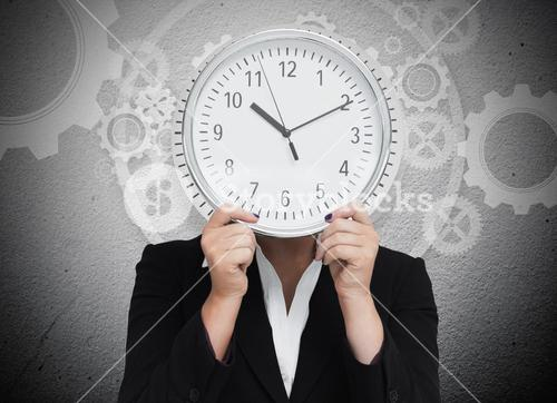 Businesswoman hiding her face with clock