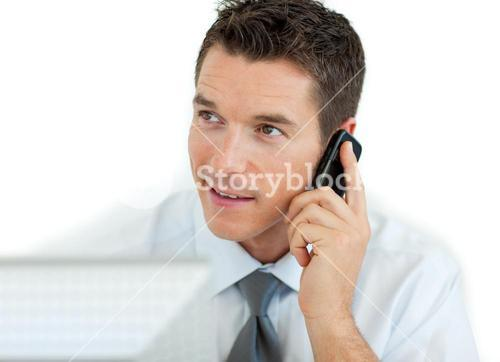 Businessman on phone working at a computer