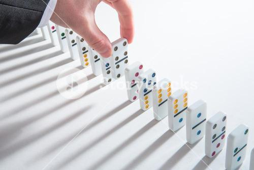 Hand placing domino into line of dominoes