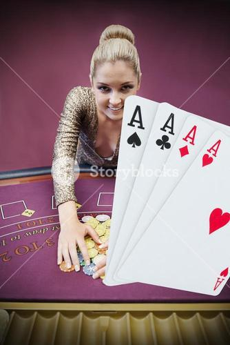 Blonde woman grabbing chips with digital hand of four aces