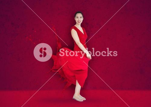Happy asian woman with red dress turning to paint splatter