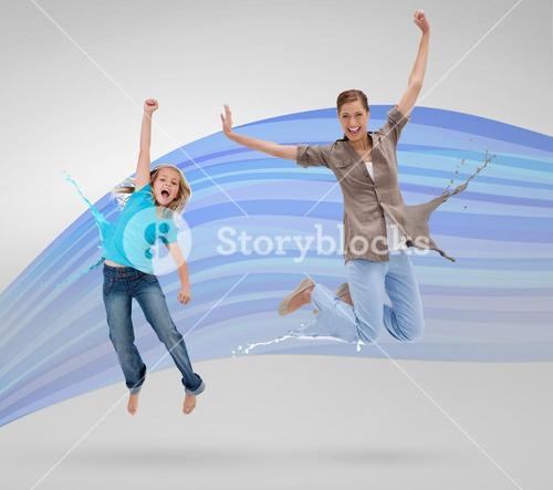 Woman and daughter jumping with clothes turning to paint splatters