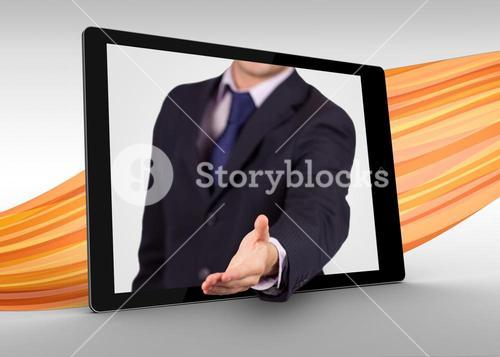 Businessman reaching out from tablet to shake hands